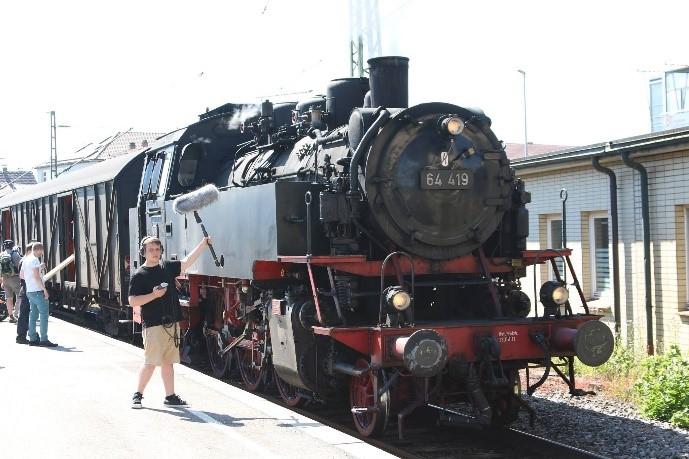 Sounddesigner Maurice Schill mit Aufnahme-Kit, vor der historischen Dampflok der Schwäbischen Waldbahn